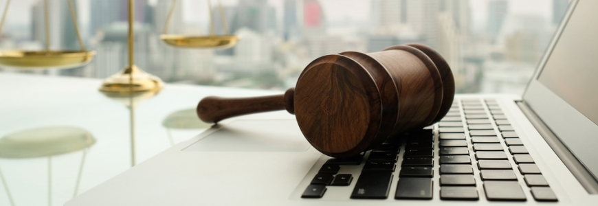 Legal weights in background with a gavel resting on a laptop