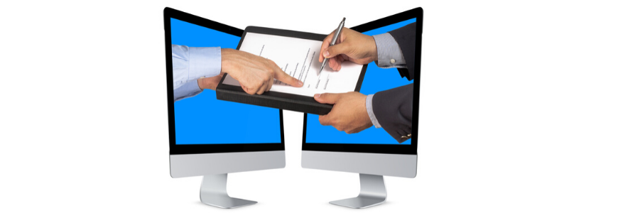 Two desktop screens facing each other with hands coming out of both and signing a document in the middle