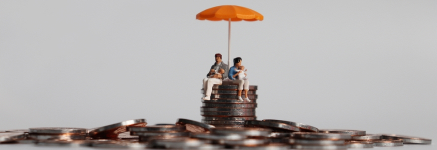 Pile of coins with a toy family sitting on top of the pile with a toy umbrella over them