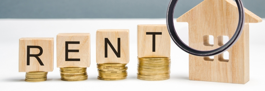 Piles of coins with wooden block on them spelling out the word rent