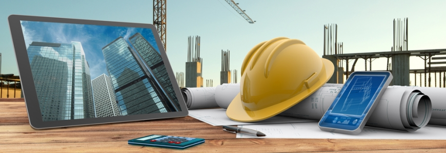 Tablet showing office buildings on a table filled with construction plans, a hard hat, calculator and documents. In the background is the start of the construction of the buildings