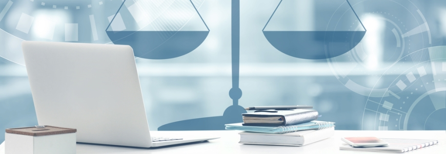 Legal scales in the background and a laptop on a desk with notepads and a pen surrounding it