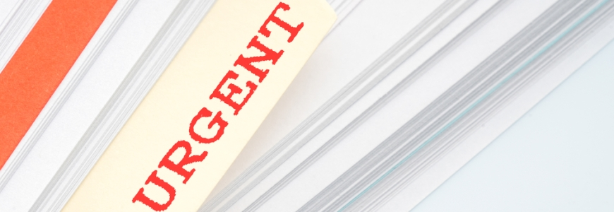 Pile of paper with a file tag sticking out with the word URGENT written in red on it