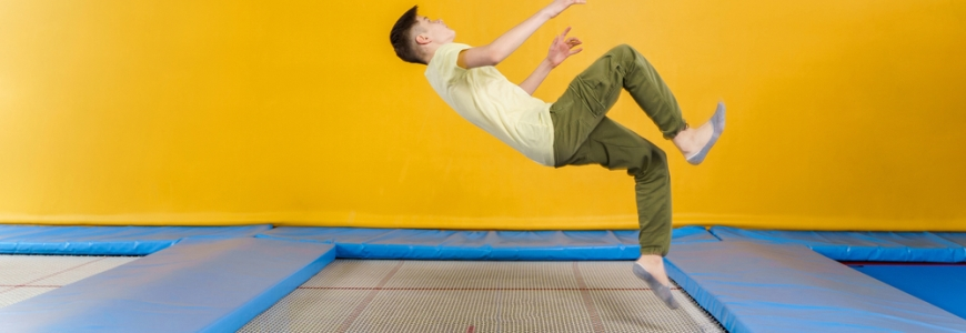 Man on a trampoline about to land on his back