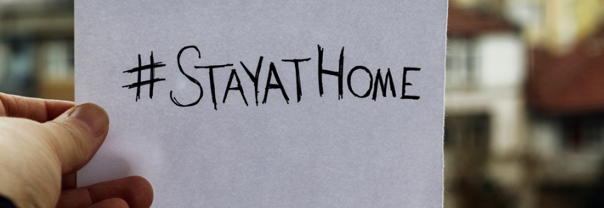 "A man's hand holding a piece of paper with ""stayathome"" handwritten on it"