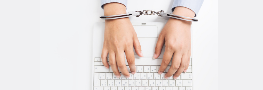 Female hands in handcuffs with laptop