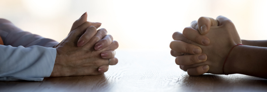 Close up clasped hands of two businesspeople negotiate at table