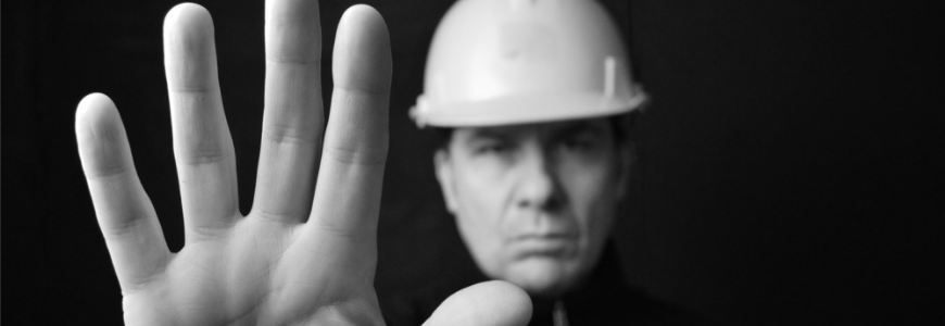 Builder in a hardhat with his hand up to indicate stop