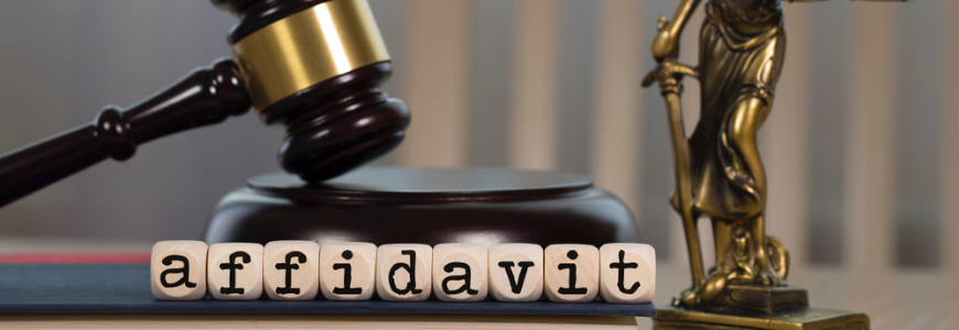 Word AFFIDAVIT composed of wooden dices. Wooden gavel and statue of Themis in the background.